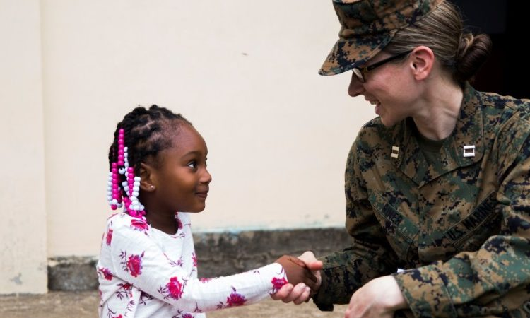 Capt. Phoebe Riner, staff judge advocate with Special Purpose Marine Air-Ground Task Force - Southern Command, shakes hands with a child at the opening ceremony for the Municipality of Trujillo school renovation projects at the Taufick Bendeck elementary school, June 15, 2017. The school is one of the infrastructure improvement projects the Marines of SPMAGTF-SC will work on during their six-month deployment in Central America, at the request of partner nation governments. (U.S. Marine Corps photo by Cpl. Melissa Martens)